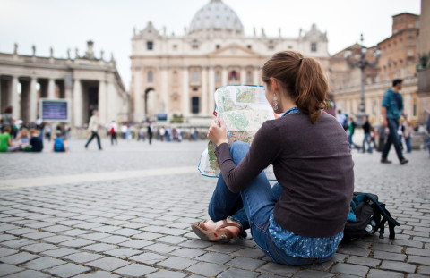 Pretty young female tourist studying a map at St. Peter's square in the Vatican City in Rome